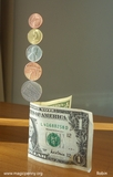 1943 US penny and other  coins balanced on a  dollar bill - robin linhope willson